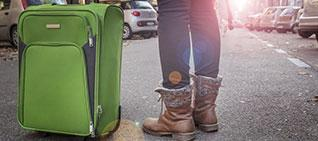 student pictured from the knees down, standing next to a suitcase